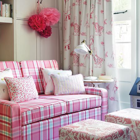 Clarke and Clarke -  Storybook Fabric Collection - A pink, blue and white checked sofa with matching patterned cushions, curtains and footstools, with a white table and lamp