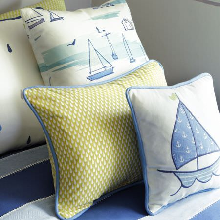 Clarke and Clarke -  Storybook Fabric Collection - Four green, white and blue patterned and nautical themed scatter cushions sitting on navy and pale blue striped fabric