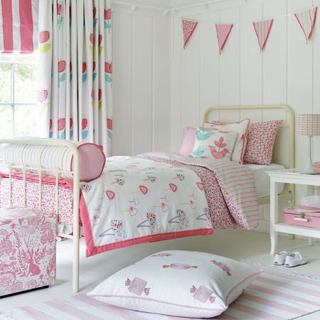 Clarke and Clarke -  Storybook Fabric Collection - White metal bed frame with pink, white and blue bedding, cushions, curtains, bunting, a blind and a rug, and a white table