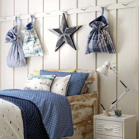 Clarke and Clarke -  Storybook Fabric Collection - White drawers and lamp, a distressed wood bed with white and blue bedding, and drawstring bags, all with a nautical theme