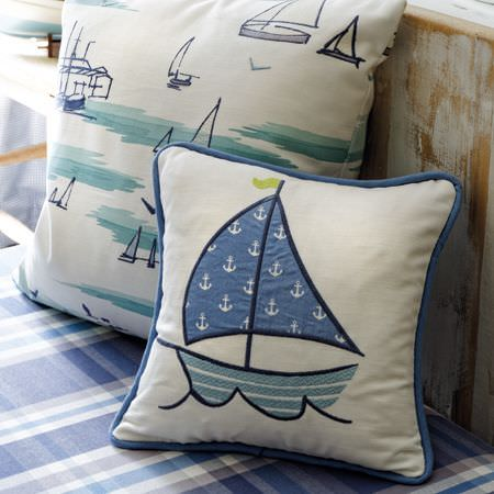 Clarke and Clarke -  Storybook Fabric Collection - Sailboat themed scatter cushions in shades of blue and white, placed on a base with a checked design in shades of blue