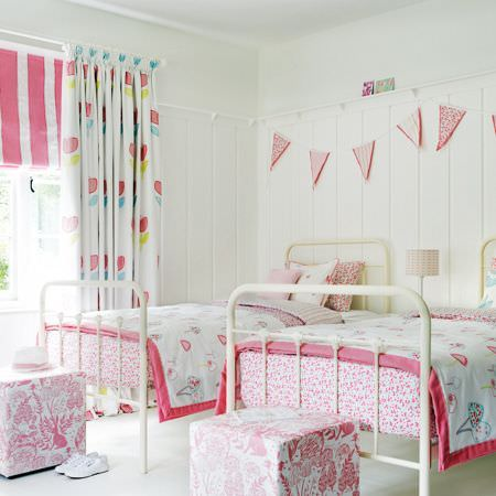 Clarke and Clarke -  Storybook Fabric Collection - Two white metal beds with pink, white, green and blue patterned bedding, curtains, footstools, cushions, bunting and a blind