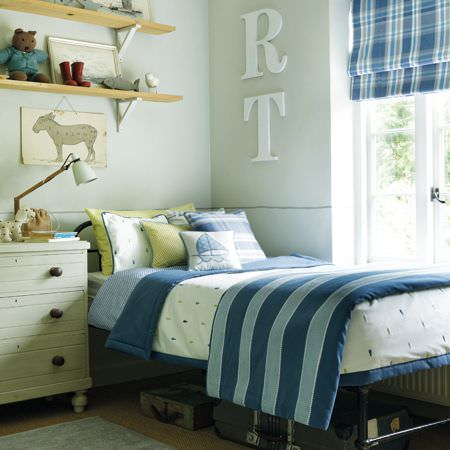 Clarke and Clarke -  Storybook Fabric Collection - Blue striped throw on patterned bedding with a checked blind and blue, green and white cushions, chest of drawers and shelves