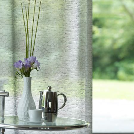 Clarke and Clarke -  Structures Fabric Collection - Translucent pale silvery grey curtains with a round glass and metal table, a white vase, a cup, saucer and a silver teapot