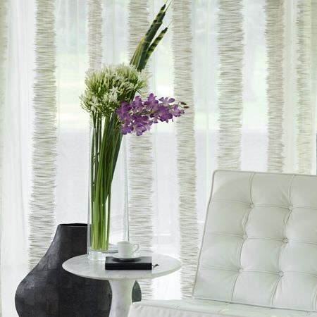 Clarke and Clarke -  Structures Fabric Collection - A tall cylindrical glass vase on a small round white table beside a white padded chair and a large round black vase