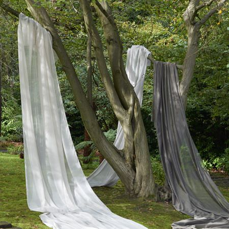 Clarke and Clarke -  Structures Fabric Collection - Trees draped with long swathes of plain, translucent white and dark grey coloured fabric