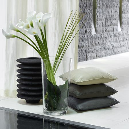 Clarke and Clarke -  Structures Fabric Collection - A jet black sculpture beside a large, clear glass vase, beside a stack of three cushions in different shades of grey