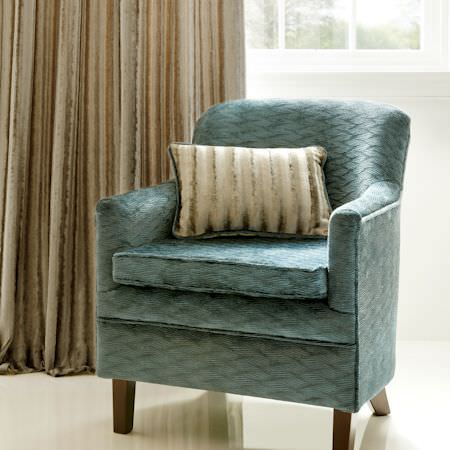 Clarke and Clarke -  Tempo Velvets Fabric Collection - Subtly patterned duck egg blue coloured armchair with wooden legs, with beige curtains and a grey-beige striped cushion