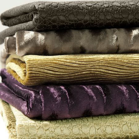 Clarke and Clarke -  Tempo Velvets Fabric Collection - Folds of five fabrics arranged in a stack; black, dark grey, gold, purple and cream, all with different patterns