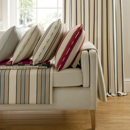 Clarke and Clarke -  Ticking Stripes Fabric Collection - Variously striped and colourful cushions, fabrics and curtain on a white upholstered couch
