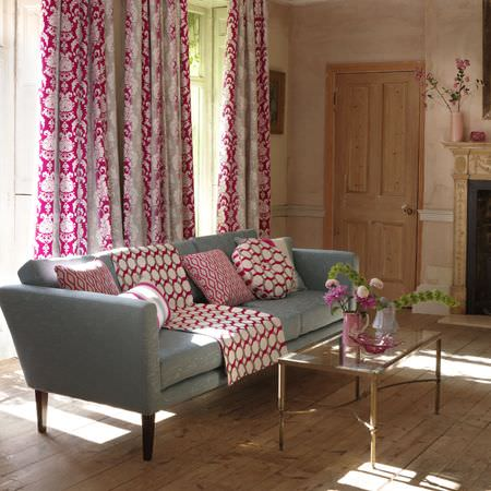 Clarke and Clarke -  Traviata Fabric Collection - Detailed hot pink, white and grey patterned curtains with matching cushions on a pale blue-grey sofa, with a glass table