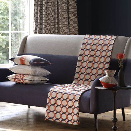 Clarke and Clarke -  Traviata Fabric Collection - A dark blue sofa with a light grey top, an orange, blue and white patterned throw, matching cushions, a table and vases