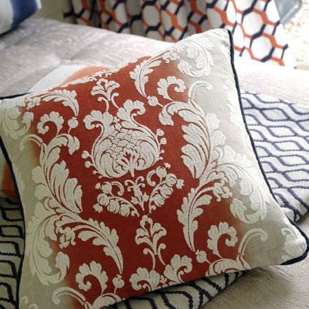 Clarke and Clarke -  Traviata Fabric Collection - A white, grey and burnt orange patterned cushion on folds of navy and white patterned fabric, on a plain cream base