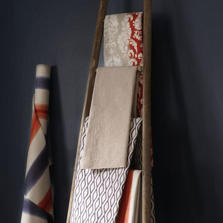 Clarke and Clarke -  Traviata Fabric Collection - A roll of striped fabric beside a wooden A-frame draped with plain and patterned fabrics in white, brown, navy and orange