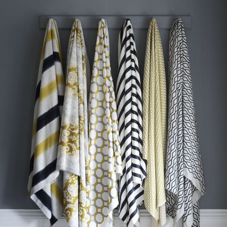 Clarke and Clarke -  Traviata Fabric Collection - Six pieces of fabric hanging from a grey coat rack, all with different patterns and designs in white, black and green-gold