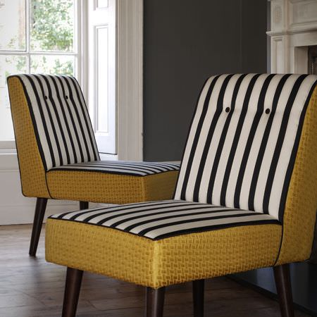 Clarke and Clarke -  Traviata Fabric Collection - Two chairs made with dark wood legs, and a combination of black and white striped fabric and light gold patterned fabric