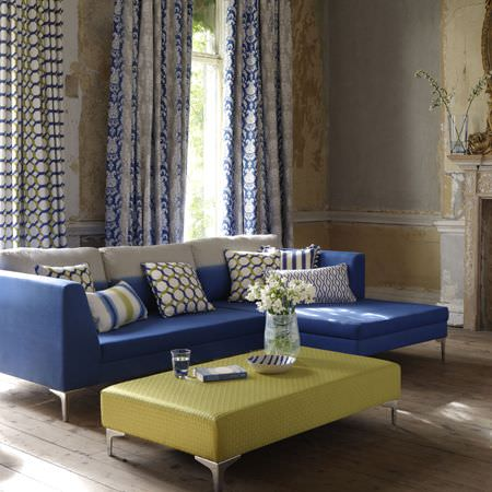 Clarke and Clarke -  Traviata Fabric Collection - Royal blue corner sofa with grey detail, a lime green coffee table, and blue and white patterned cushions and curtains