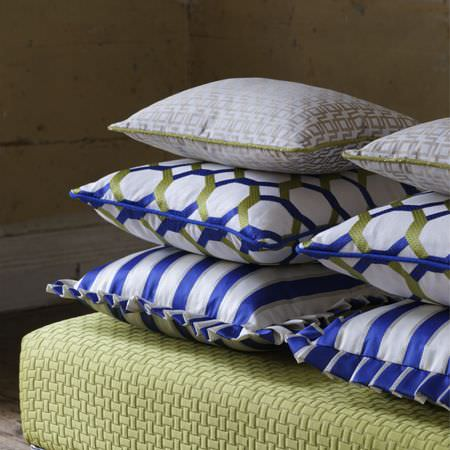 Clarke and Clarke -  Traviata Fabric Collection - A lime green seat cushion beneath six scatter cushions featuring patterns and stripes in white, olive green and Royal blue