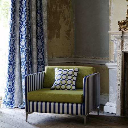 Clarke and Clarke -  Traviata Fabric Collection - A striped armchair with green back and seat cushions, a geometric patterned cushion and blue and white patterned curtains
