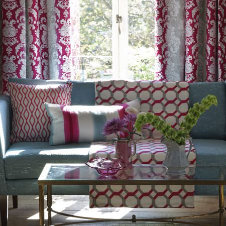 Clarke and Clarke -  Traviata Fabric Collection - A wood and glass coffee table with a light blue sofa and pink, blue and white patterned and striped curtains and cushions
