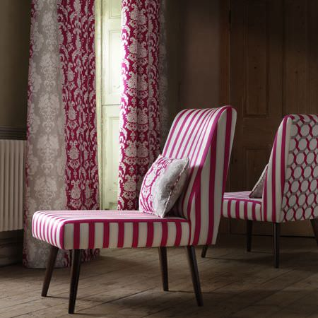 Clarke and Clarke -  Traviata Fabric Collection - Pink and white striped chairs made with patterned backs and dark wood legs, with pink, white and grey patterned curtains