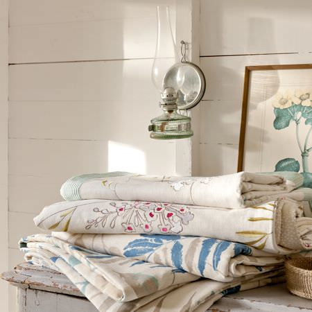 Clarke and Clarke -  Wild Garden Fabric Collection - Folds of fabric with floral patterns in a rustic, renovated setting with a traditonal lamp and framed picture