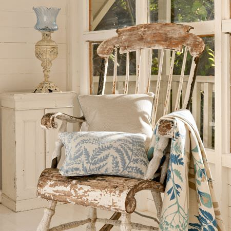 Clarke and Clarke -  Wild Garden Fabric Collection - A quilt and cushions with floral patterns in a rustic, renovated setting with an old fashioned lamp and rocking chair