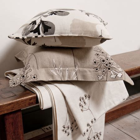 Clarke and Clarke -  Wild Garden Fabric Collection - Cushions and a throw of floral fabrics in white, black and grey on an antique bench in a rustic setting