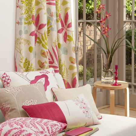 Clarke and Clarke -  Wild Garden Fabric Collection - Floral summer curtains mainly pink and green. light beige sofa with beige, cream and pin patterned cushions.