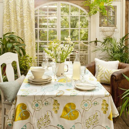 Clarke and Clarke -  Wild Garden Fabric Collection - A plant filled dining room with big windows and gold, white and brown fabrics used for tablecloth, cushions and upholstery