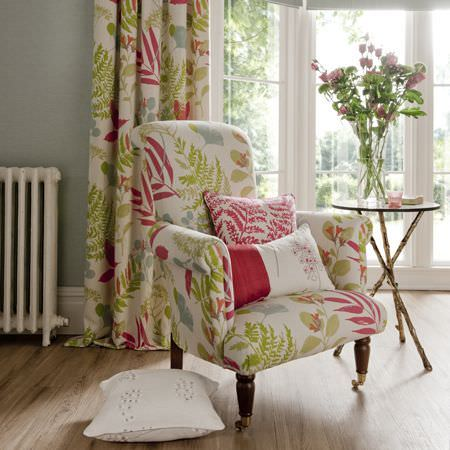 Clarke and Clarke -  Wild Garden Fabric Collection - Bright summery fabric with floral motifs used to upholster an armchair and for cushions and curtains in a light setting