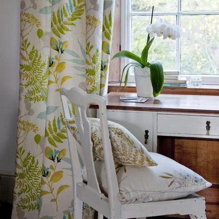 Clarke and Clarke -  Wild Garden Fabric Collection - Vintage furniture and chairs, a flowering plant pot and cushions and curtains in an organic pattern of greens, yellows, greys and white