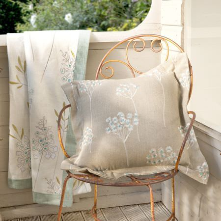 Clarke and Clarke -  Wild Garden Fabric Collection - A sunny porch with a wire chair and floral fabric in colours of white, blue, grey and gold, used for a quilt and cushion