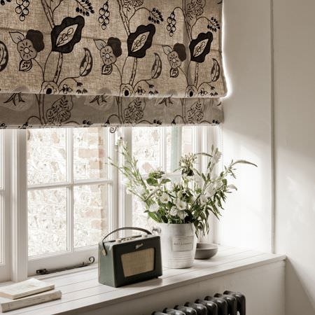 Clarke and Clarke -  Wild Garden Fabric Collection - Roman blinds with a black and white floral pattern in a white room, with a radio, flowers, books and a bowl on the window ledge