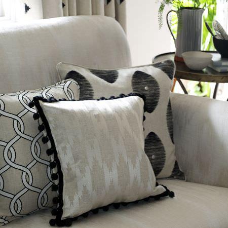 Clarke and Clarke -  Zanzibar Fabric Collection - A round table, a white sofa with three cushions featuring patterns in white, grey, silver and black, with fringed edging