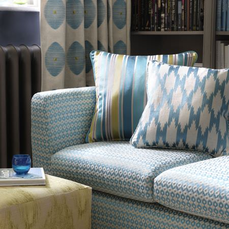 Clarke and Clarke -  Zanzibar Fabric Collection - A blue and white patterned sofa with 2 blue, white and green patterned cushions, matching curtains and a green-cream footstool