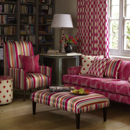 Clarke and Clarke -  Zanzibar Fabric Collection - A brightly coloured striped armchair and large footstool, with a hot pink patterned sofa, curtains and cushions