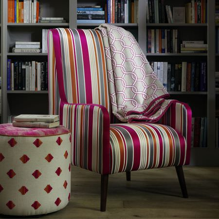 Clarke and Clarke -  Zanzibar Fabric Collection - Pink, grey and white fabric draped over a brightly coloured striped armchair with a pink and white patterned round footstool