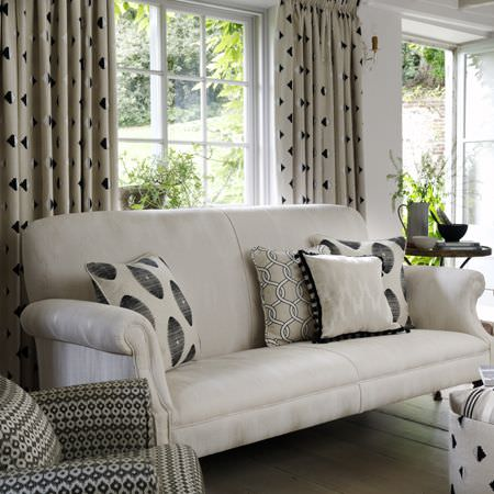Clarke and Clarke -  Zanzibar Fabric Collection - Black and off-white curtains with a plain off-white sofa, a patterned armchair and plain and patterned scatter cushions