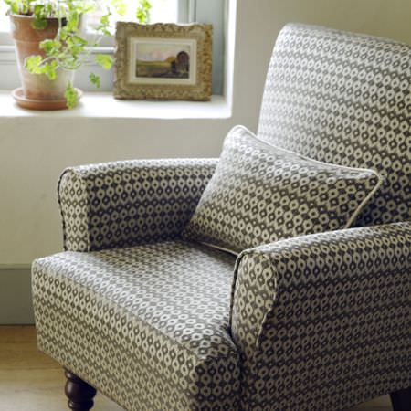 Clarke and Clarke -  Zanzibar Fabric Collection - A small armchair and rectangular cushion, both covered with fabric made with a very small grey and off-white pattern