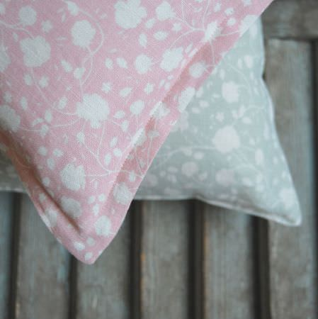 Cloth and Clover -  Cloth and Clover Collection - A rustic wood chair with two floral scatter cushions, featuring simple designs in white and pastel shades of blue and pink