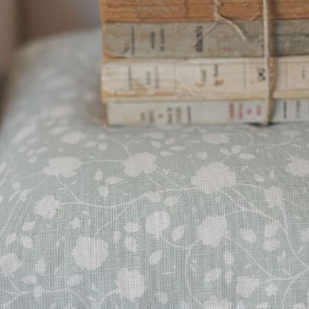 Cloth and Clover -  Cloth and Clover Collection - A stack of books tied with twine, placed on a cushion covered with pale blue and white fabric with a simple floral pattern