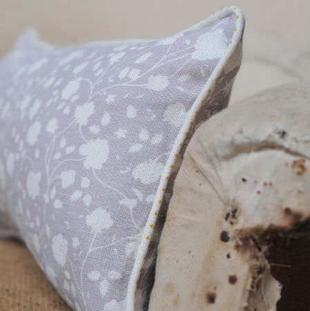 Cloth and Clover -  Cloth and Clover Collection - A rectangular light purple and white floral patterned scatter cushion, sitting on a distressed cream fabric armchair