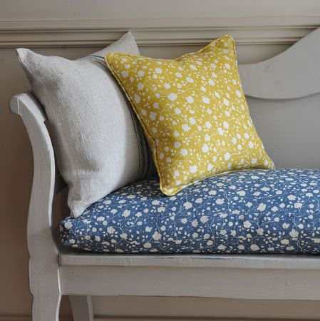 Cloth and Clover -  Cloth and Clover Collection - A plain white cushion, and floral scatter and seat cushions in white, gold and navy, on a white painted wooden bench