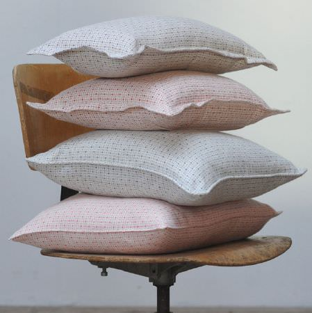 Cloth and Clover -  Cloth and Clover Collection - Four white,grey, red, blue and pale pink cushions featuring a small geometric print, sitting on a wooden swivel chair