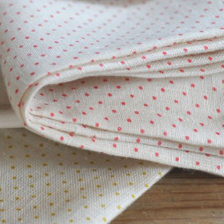 Cloth and Clover -  Cloth and Clover Collection - Two pieces of folded chalk white coloured fabric, both with small dot patterns, one in pink-red and one in gold