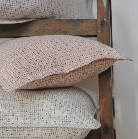 Cloth and Clover -  Cloth and Clover Collection - Three cushions stacked in a wooden ladder, all featuring small geometric shapes in white, red, blue and grey