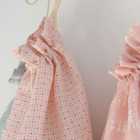 Cloth and Clover -  Cloth and Clover Collection - Two drawstring bags made from candy pink and white fabrics,featuring geometric designs and fun people and animal prints