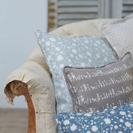 Cloth and Clover -  Cloth and Clover Collection - Four floral, geometric, and fun people and animal print cushions in white, blue and grey shades, on a distressed armchair