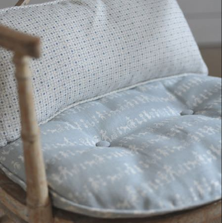 Cloth and Clover -  Cloth and Clover Collection - A wooden chair with a pale blue and white patterned seat cushion, and a scatter cushion with grey and white geometric shapes